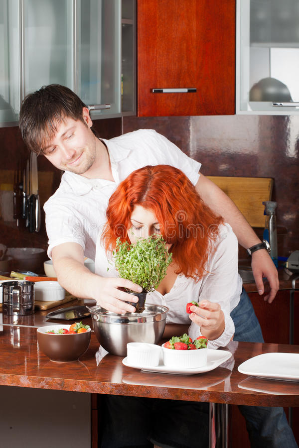 Young pair on the kitchen: bring her flowers. A young man presents potted thyme to his girlfriend while she eats strawberry and ready to cook royalty free stock image