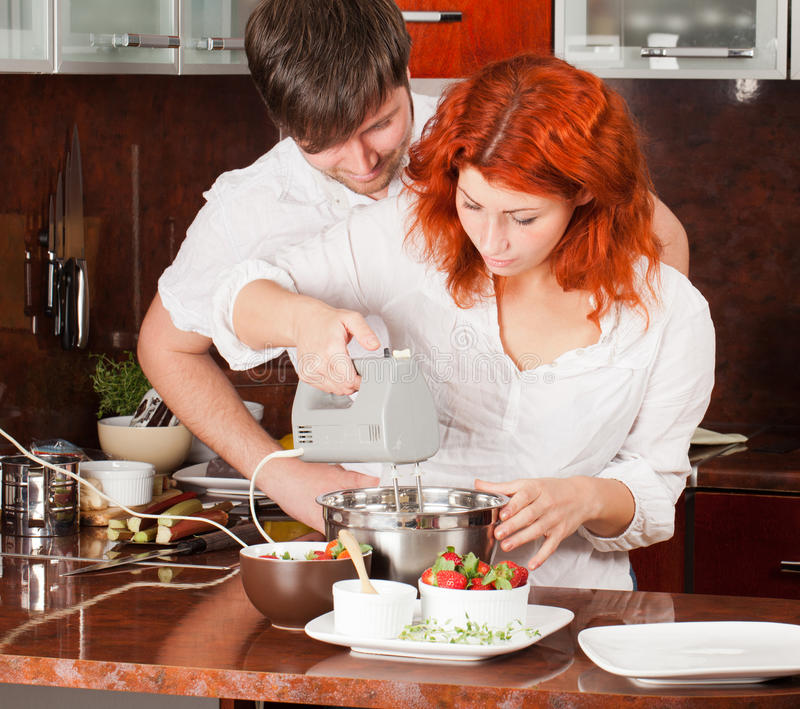 Young pair on the kitchen: making pastry together. A young men helps his girlfriend in making pastry stock image