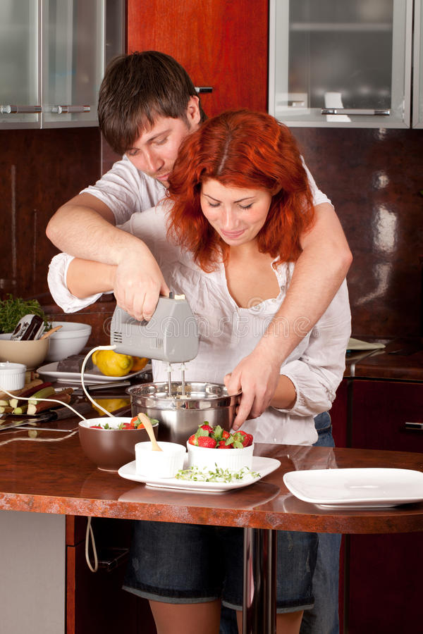 Young pair on the kitchen: making pastry together. A young men helps his girlfriend in making pastry royalty free stock photo