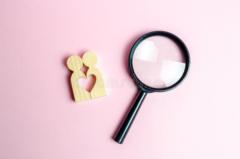 A young pair of lovers and a magnifying glass. The concept of finding a couple on Valentine`s Day. Declaration of love stock photography