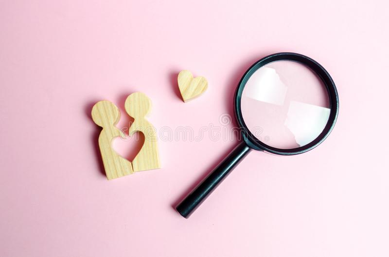 A young pair of lovers and a magnifying glass. Search for love and creation of strong love relationships. Dating and flirt royalty free stock images