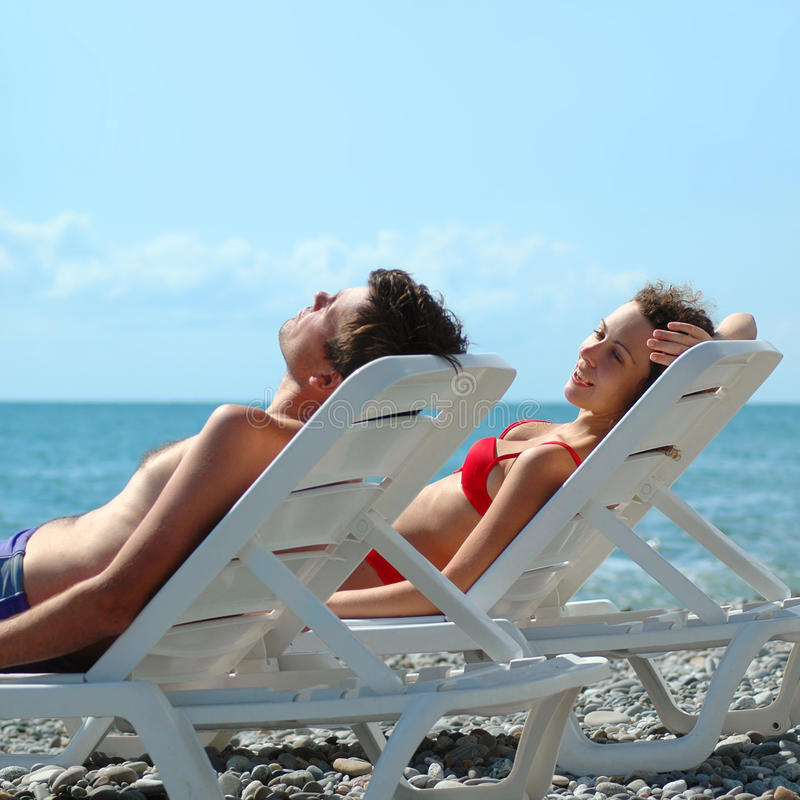 Free Young Pair Reposes In Chaise Lounge Royalty Free Stock Photo - 13261305