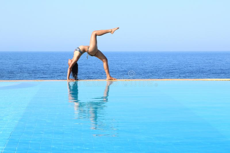 Young woman exercising yoga on edge of pool by sea royalty free stock photos