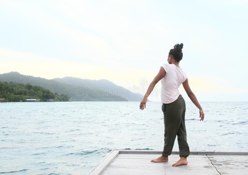 Girl standing on jetty by sea royalty free stock photos