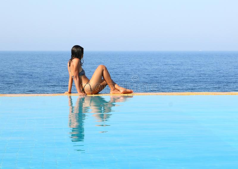 Young woman sitting on edge of pool by sea royalty free stock photos