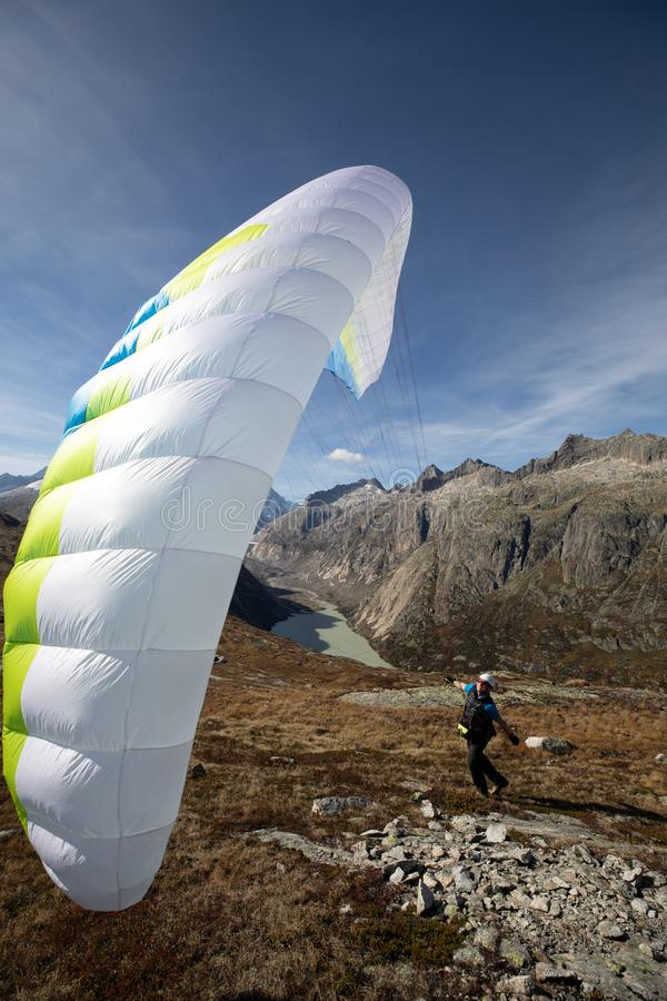 Young paraglider pilot uses his paraglider to play with the wind in the Swiss Alps, the so-called ground handling. Location: Grimsel, Switzerland stock image