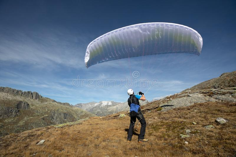 Young paraglider pilot uses his paraglider to play with the wind in the Swiss Alps, the so-called ground handling. Location: Grimsel, Switzerland stock images