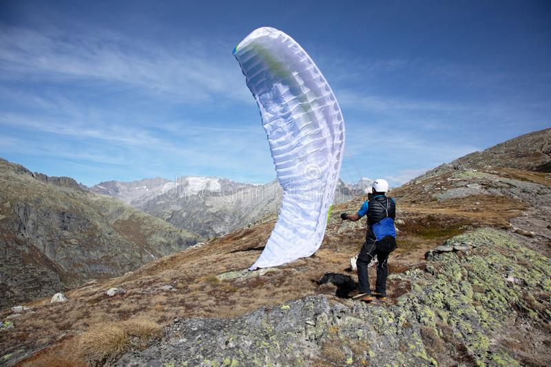 Young paraglider pilot uses his paraglider to play with the wind in the Swiss Alps, the so-called ground handling. Location: Grimsel, Switzerland stock photo