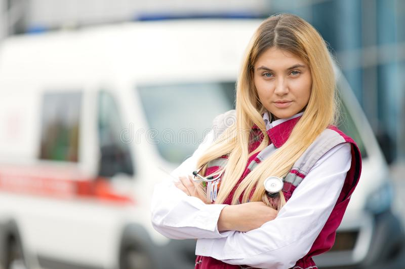 Young paramedic female with phonendoscope at emergency car background royalty free stock photography