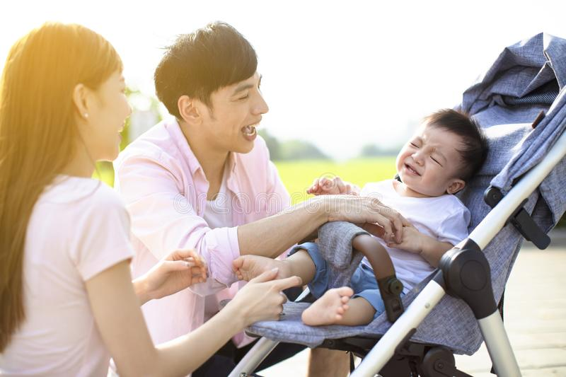 Young parents with baby crying in the carriage royalty free stock image