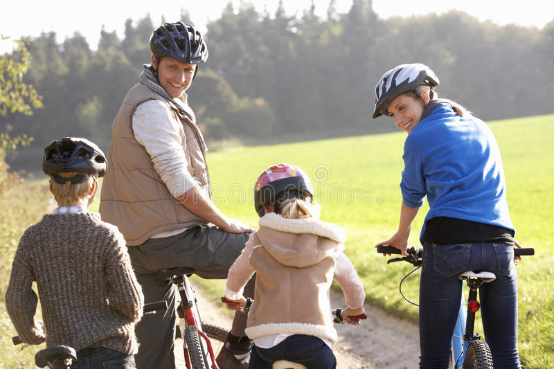 Young parents with children ride bikes in park stock photos