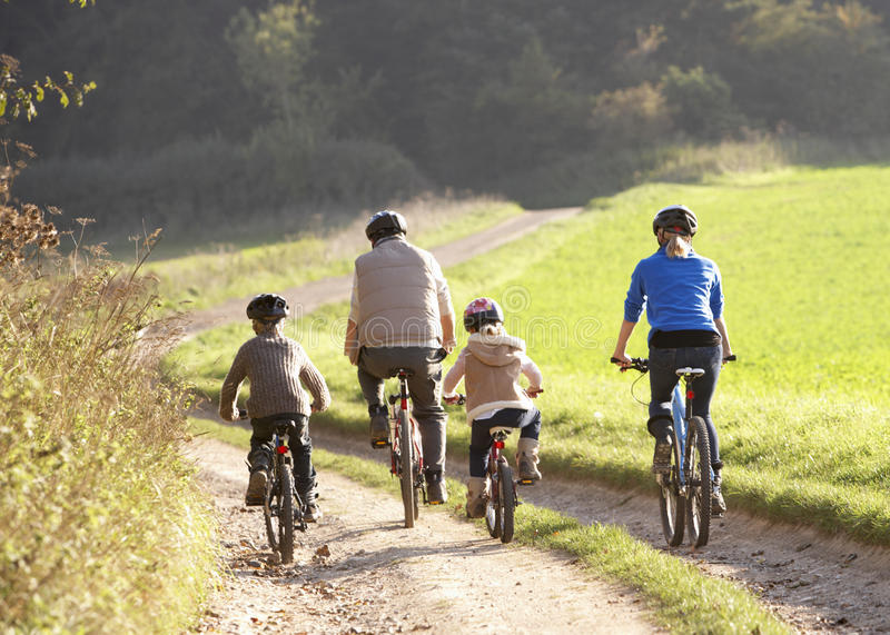 Young parents with children ride bikes in park stock image