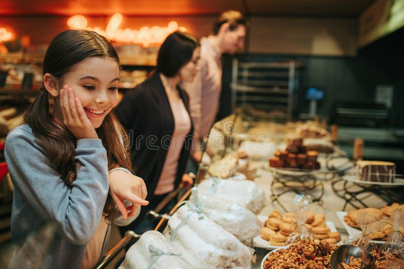 Young parents and daughter in grocery store. Amazed very happy girl stand at shelf with candy and look at them stock photography