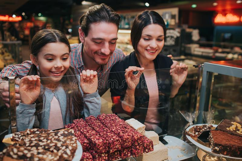Young parents and daughter in grocery store. Delicious tasty candy and sweets on shelf. Family look at it and smile. Hungry and want to eat stock images