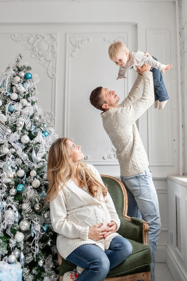 Young parents fool around and play with little son. Happy family having fun at home. Christmas morning in bright living stock images