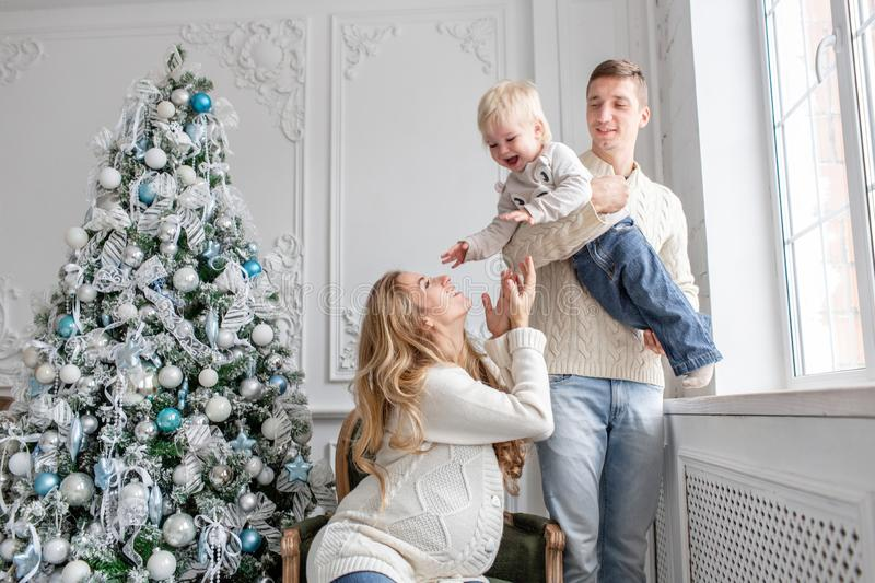 Young parents fool around and play with little son. Happy family having fun at home. Christmas morning in bright living royalty free stock images