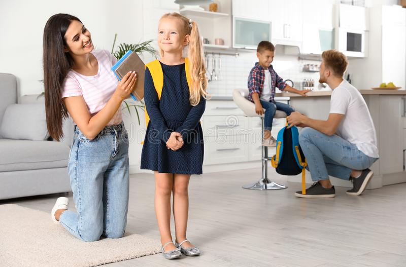 Young parents helping little children to prepare for school stock photography