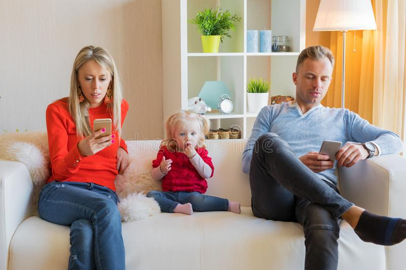 Young parents ignore their kid and looking at their mobile phones royalty free stock images