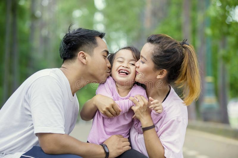 Young parents kissing their daughter in the park stock images
