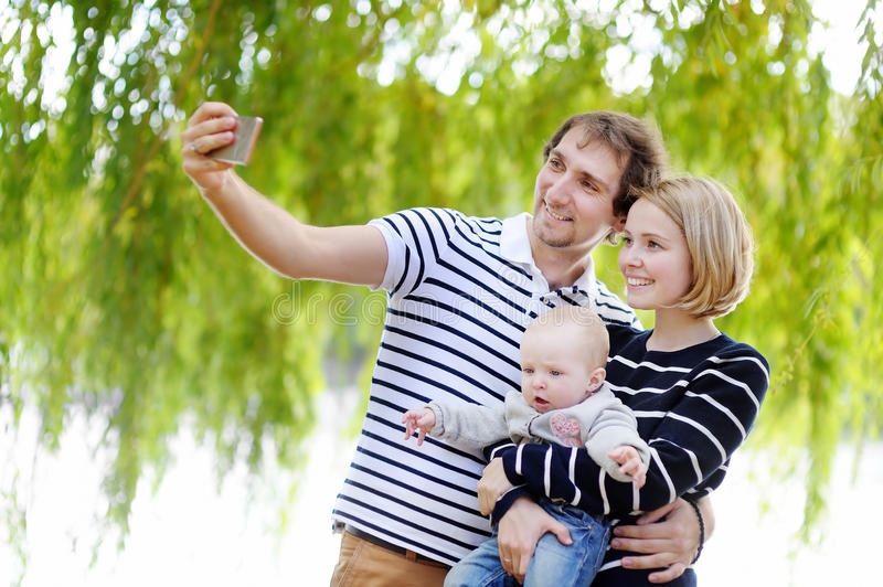 Young parents making a self portrait with their baby girl royalty free stock image