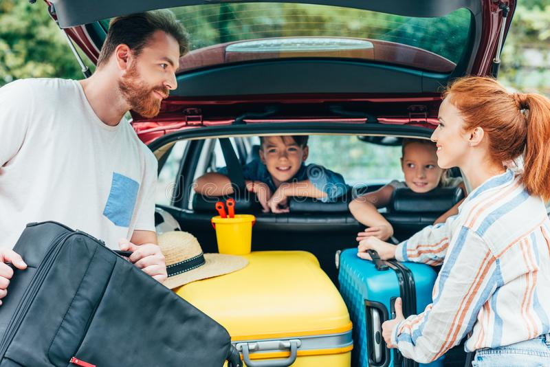 young parents packing luggage in trunk of car with kids royalty free stock photography