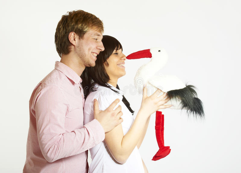 Young parents with stork toy. Young parents expecting a baby holding a stork toy in their hands as a symbol for their upcoming baby, image isolated on grey stock photography