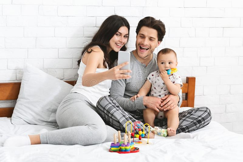 Young parents taking selfie with their adorable baby royalty free stock photography