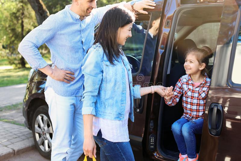 Young parents taking their little child to school. By car stock photos