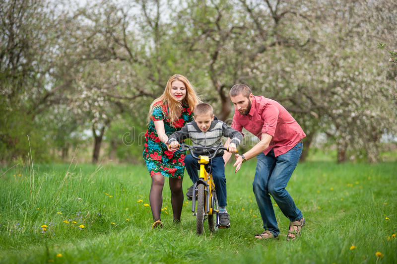 Young parents teaching his son to ride a bike. In spring garden. Family having fun against the background of blooming trees, dandelions and fresh greenery stock photo