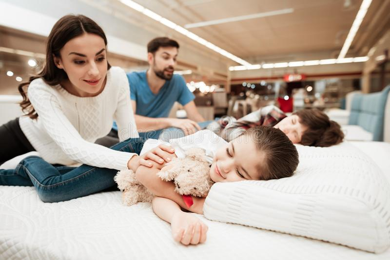 Young parents wake sleeping children on mattress in orthopedic furniture store. Testing softness of mattress. Choosing mattress in store royalty free stock photography