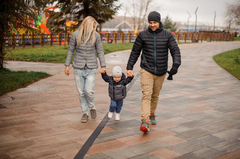 Young parents walking down the street with a little son stock images