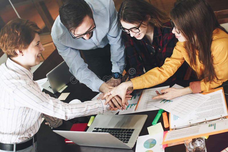 Young partners make an agreements about joint project. Group of coworkers working together оn project in loft office. Business people brainstorm concept stock image