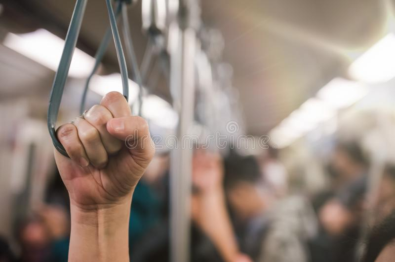 Young passenger woman hand holding Handle on the train or on the bus for safety. Safety travel trip royalty free stock image