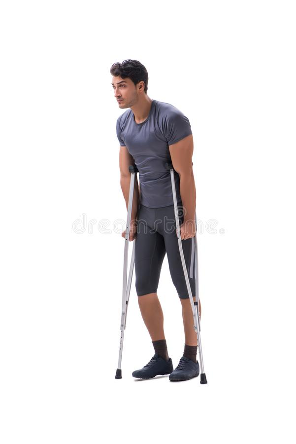 Young patient athlete sportsman suffering an injury trauma with. Crutches isolated on white stock photography