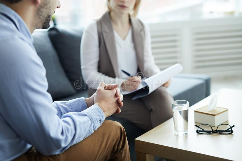 Patient in trouble. Young patient of counselor sitting on couch by table, talking about his problems and waiting for advice royalty free stock photo