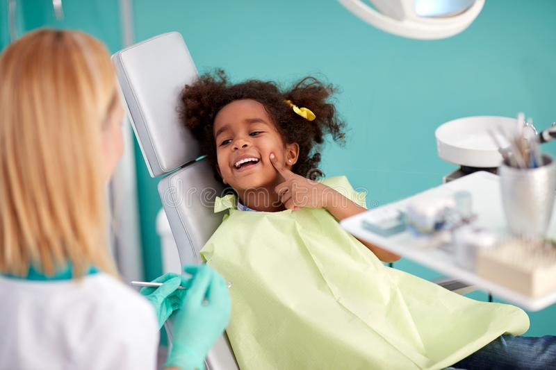 Young patient in dental clinic show with finger tooth for repair. Ing to female assistant royalty free stock photography