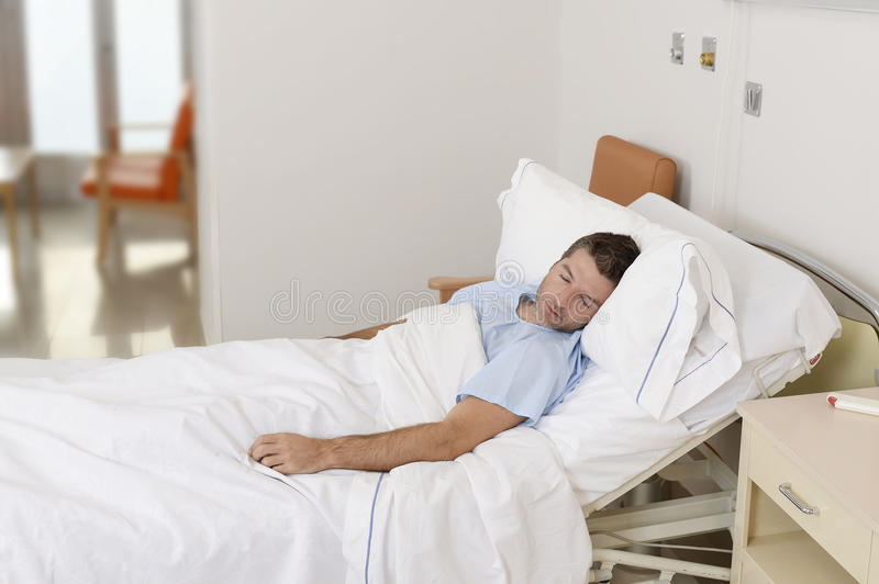 Young patient man lying at hospital bed resting and sleeping having serious medical condition stock images