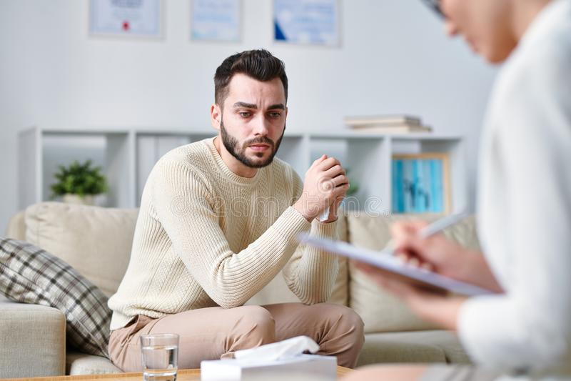 Waiting for advice. Young patient of psychotherapist sitting on couch and looking attentively at counselor making notes on paper royalty free stock photography