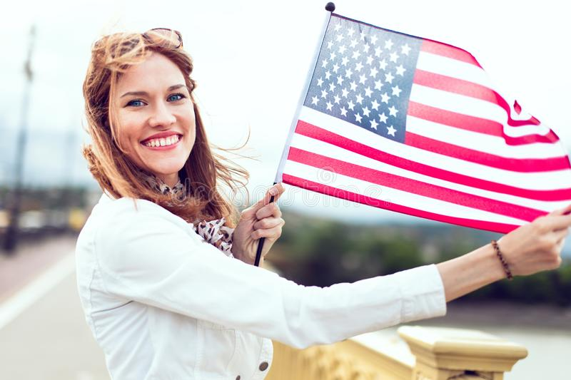Young patriot woman with toothy smile stretching star spangled banner. Happy young patriot urban woman with toothy smile stretching star spangled banner stock images