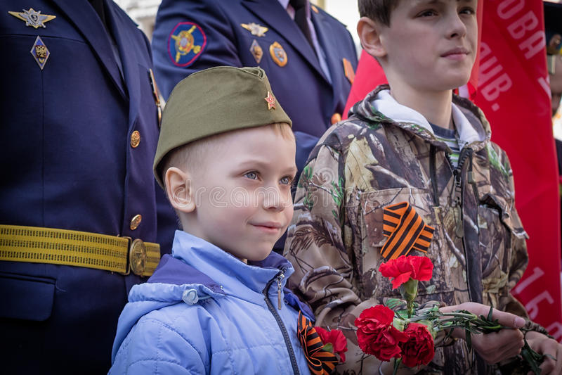 Young patriots worn forage cap with red star sign. Two young patriots worn forage cap with a star sign and bouquet of carnations in their hands a stock photos