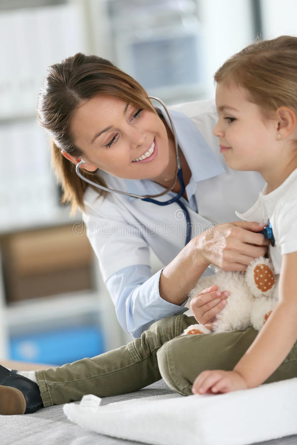 Young pediatrician doctor examining little girl with stethoscope royalty free stock photo