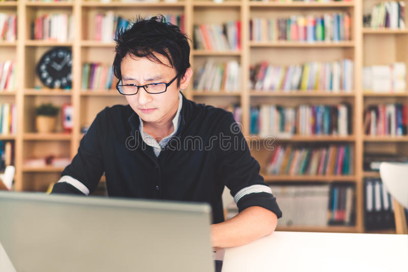 Young pensive Asian man working on laptop at home office or library with serious face, bookshelf blur background with copy space. Young pensive Asian man working royalty free stock photo