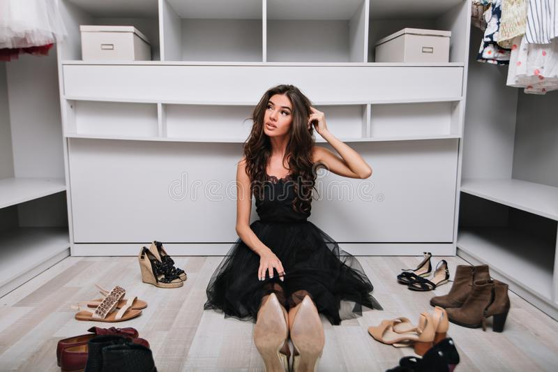 Young pensive beautiful brunette girl choosing shoes in her wardrobe sitting on the floor. She is dressed in a black royalty free stock image