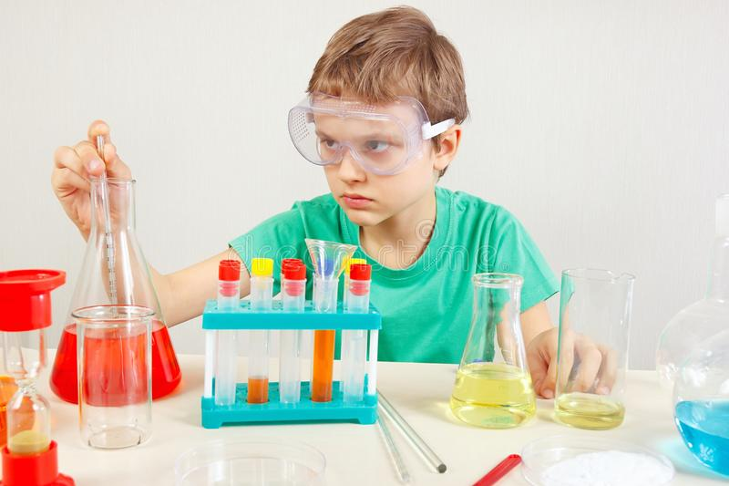 Young pensive boy in safety goggles doing chemical experiments in laboratory. Young pensive boy in safety goggles doing chemical experiments in the laboratory royalty free stock image