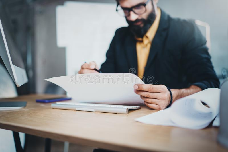 Young pensive coworker working at sunny work place loft while sitting at the wooden table.Man analyze paper document. Blurred background.Horizontal.Closeup royalty free stock photo