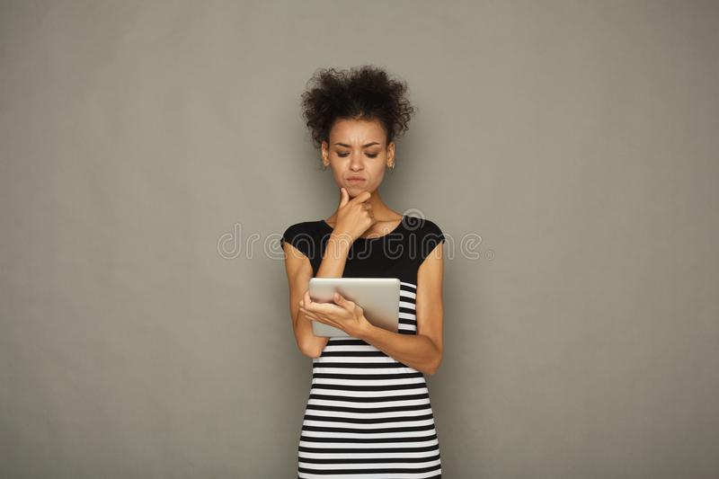 Young pensive girl using digital tablet stock photography