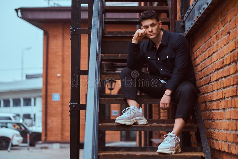A young pensive guy sitting on stairs outside near a building with the industrial exterior. A young pensive guy wearing a shirt sitting on stairs outside near a royalty free stock photography