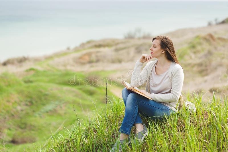 Young pensive relaxed woman in light casual clothes sitting on grass studying reading book on green field background. Student learning, education. Beautiful royalty free stock images