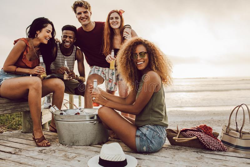 Friends hanging out at beach on vacation. Young people around beverage tub sitting at beach. Beautiful women with friends hanging out at beach on vacation stock image