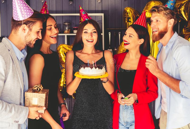 Young people around birthday cake. Having party royalty free stock image